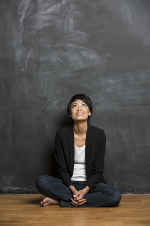 Happy Asian woman standing in front of a dark chalkboard  The chalk board is blank waiting for a message  Stock Photo