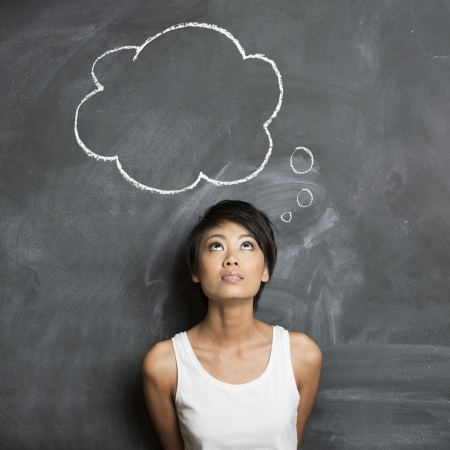 暗い黒板に描かれた思想バブル手の下で立って幸せなアジアの女性
