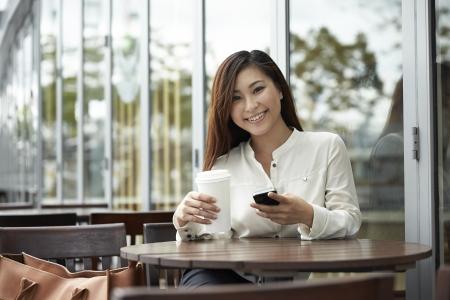 Portrait d'une femme d'affaires chinoise en utilisant un téléphone intelligent dans un café