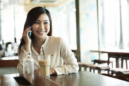 Candid image of a Chinese businesswoman talking on phone in a cafe photo