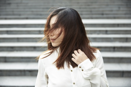 wind blown hair: A Chinese business woman standing with her hair blown by the wind over face