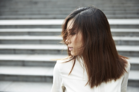 wind blown hair: A Chinese woman standing with her hair blown by the wind over face