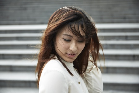 face centered: A Chinese business woman standing with her hair blown by the wind over face