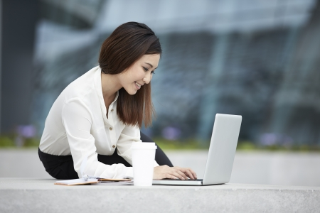 Young Chinese office worker using a laptop outside  Asian Business woman using laptop outside  photo
