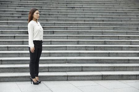 A portrait of a young Chinese businesswoman standing outside. photo