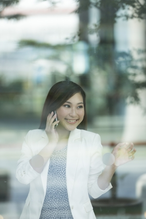 Portrait of a Chinese Business woman using a smartphone and looking through a window photo