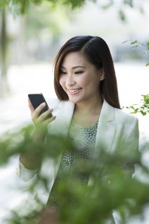 Femme d'affaires asiatique à l'aide d'un téléphone intelligent. Heureux sourire femme d'affaires chinoise marcher dans la rue en utilisant téléphone portable.