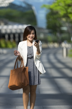 Asian Businesswoman using a smart phone. Happy smiling Chinese business woman walking in street using cellphone. Stock Photo