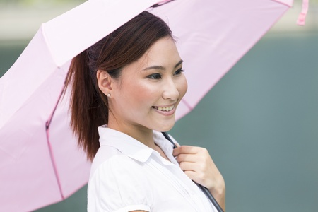 sun umbrella: Young Chinese business woman holding an umbrella outdoors