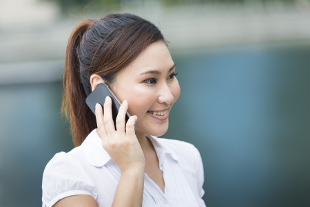 Asian Businesswoman using a smart phone. Happy smiling Chinese business woman walking in street using cellphone. Stock Photo - 21023695