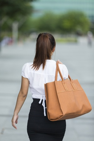 Young Asian businesswoman walking in the city with back to camera holding a big bag photo