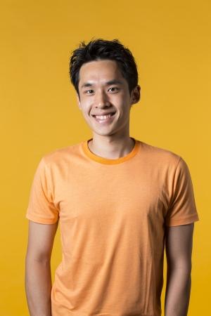 Portrait d'un homme asiatique debout contre un fond jaune.