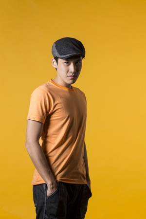 Portrait of Asian man standing against yellow background. photo