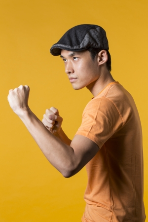 Portrait of Asian man throwing a punch. Standing against yellow background. photo