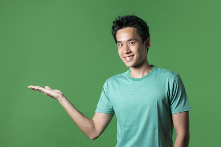 Portrait of a happy Asian man holding out her hand to show your message. Green background. photo