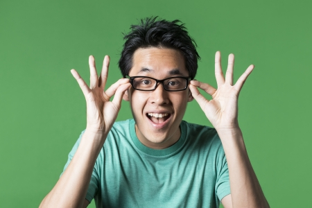 standing against: Surprised and amazed looking Asian man standing against green background. Stock Photo