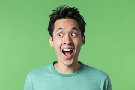クローズ アップ男の肖像幸せアジア中国左に見ています。緑の背景。 写真素材
