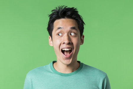 the left: Closeup portrait of a happy AsianChinese man looking to left. Against green background. Stock Photo