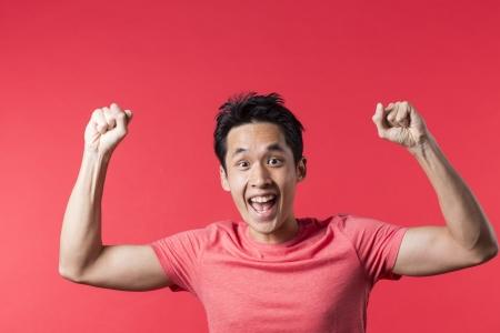 Enthousiaste homme asiatique de célébrer avec son bras. En face de fond rouge.
