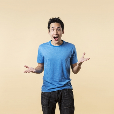 Surprised and amazed looking Asian man standing against cream background. photo