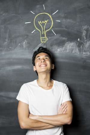 Happy Asian man standing in front of chalkboard with light bulb drawn above his head. Concept about ideas. photo