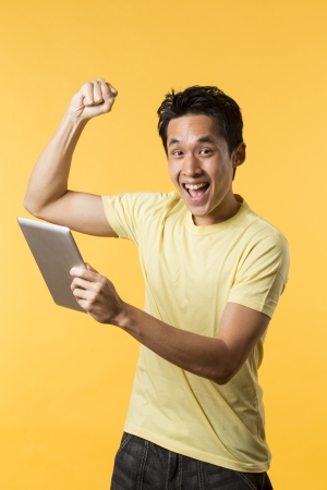Cheerful Asian man celebrating with his arm up & holding a tablet PC. In front of Yellow background. photo