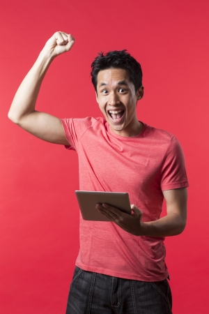 Cheerful Asian man celebrating with his arm up & holding a tablet PC. In front of Red background. photo