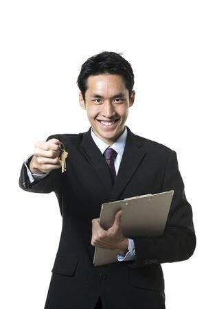 Chinese estate agent holding house keys. Isolated on a white background. photo