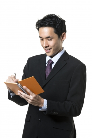 take a note: Handsome Chinese business man taking notes. Isolated on a white background.