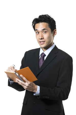 Handsome Chinese business man taking notes. Isolated on a white background. photo