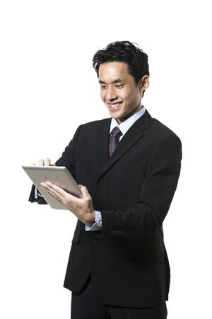 businessman standing: Cheerful Asian man using a tablet PC. Isolated on white background.