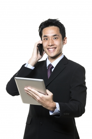 Chinese businessman with a tablet computer and talking on phone. Isolated on a white background. photo