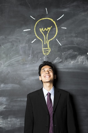 Portrait of a Asian business man standing next to a blackboard. Stock Photo