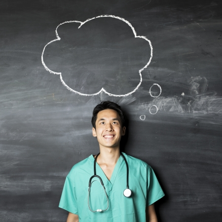 Portrait of a Asian Doctor wearing green scrubs looking at a speech bubble drawn on a blackboard.