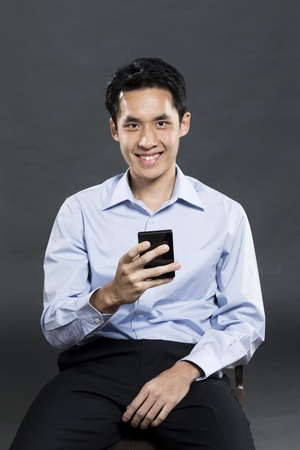 chinese adult: Portrait of a stylish Asian business man using a smart phone. Dark grey background