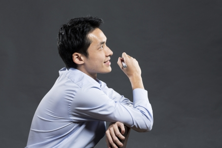 asian man face: Portrait of a stylish Asian business man sitting on a chair and looking to right. Dark grey background