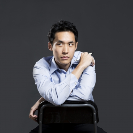 Portrait of a stylish Asian business man sitting on a chair and looking to left. Dark grey background photo