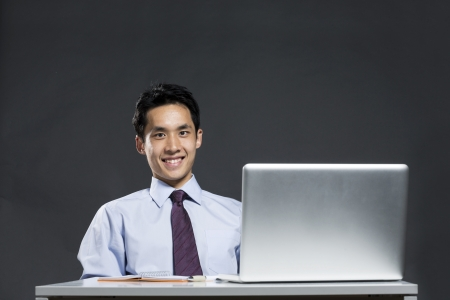 asian business man: Portrait of an Asian business man sitting at a desk working with a laptop. Dark grey background Stock Photo