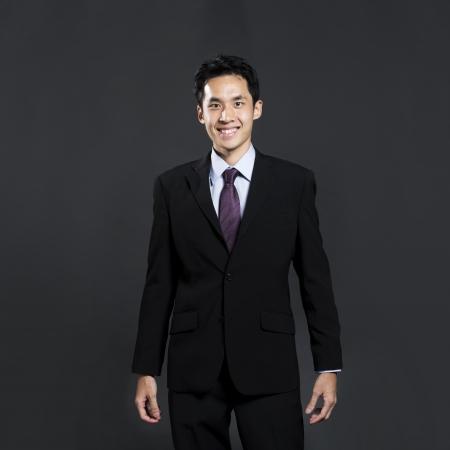 Portrait d'un homme d'affaires asiatique élégant debout devant un fond gris foncé