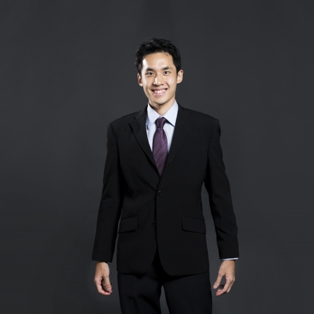 Portrait of a stylish Asian business man standing in front of a dark grey background