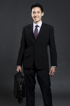Portrait d'un homme d'affaires asiatique élégante tenant une mallette. Fond gris foncé Banque d'images