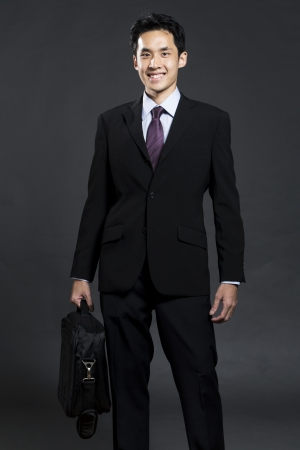 Portrait of a stylish Asian business man holding a briefcase. Dark grey background