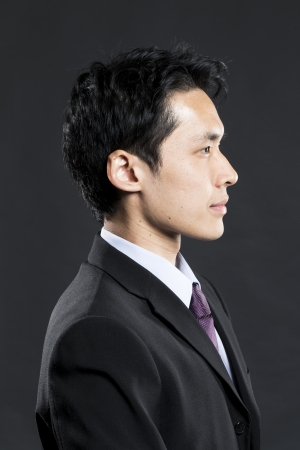 serious: Portrait of a young Asian business man looking away. Dark grey background