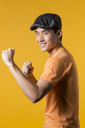Playful Asian man throwing a punch. Yellow background. photo