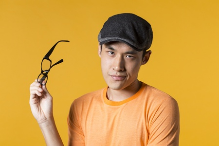 Portrait of serious Asian man standing against yellow background. photo