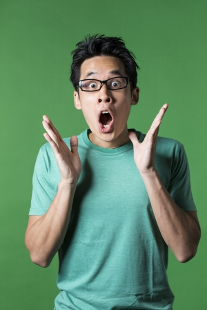 shocked face: Surprised and amazed looking Asian man standing against green background. Stock Photo