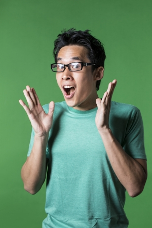 excited: Surprised and amazed looking Asian man standing against green background. Stock Photo