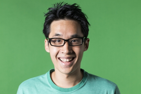 Portrait of an excited Asian man looking at camera. Green background Stock Photo