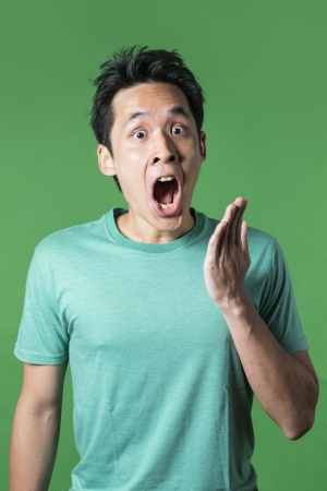 Surprised and amazed looking Asian man standing against green background. photo