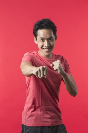 Portrait of a Playful Asian man standing with his fist up ready for a fight. Against red background. photo